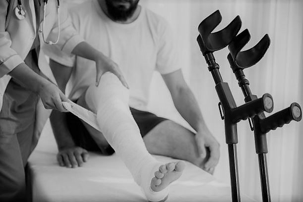 man with crutches having his injured leg bandaged by doctor